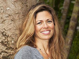 Portrait of Christine Waara leaning on grand palm