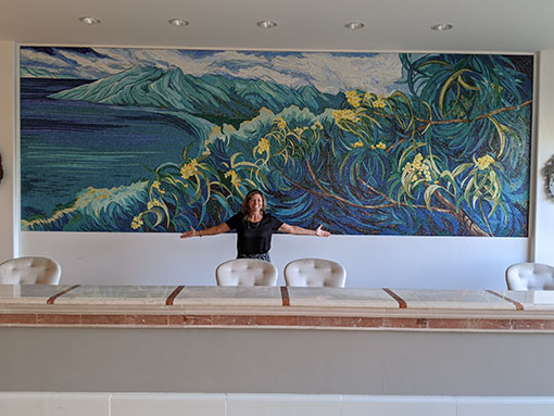 Maui artist Christine Waara standing in front of the tile mosaic in the lobby of the Fairmont Kea Lani hotel in Maui